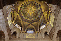 Dome above the maqsura, a richly decorated ribbed vault with small dome in front of the mihrab, redecorated under Al-Hakam II in 961, in the Cathedral-Great Mosque of Cordoba, in Cordoba, Andalusia, Southern Spain. Below the dome are intricately carved interlacing fluted arches. The ceiling is decorated with kufic script, floral motifs, and a sunburst radiating from a tiny central star, with light coming from 8 latticed side windows. The first church built here by the Visigoths in the 7th century was split in half by the Moors, becoming half church, half mosque. In 784, the Great Mosque of Cordoba was begun in its place and developed over 200 years, but in 1236 it was converted into a catholic church, with a Renaissance cathedral nave built in the 16th century. The historic centre of Cordoba is listed as a UNESCO World Heritage Site. Picture by Manuel Cohen