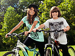Two happy smiling children on their bicycles in a park, brother and sister, 10 and 13, enjoying sunny summer day.