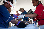 Doctors treat a victim of Haiti's recent earthquake at a field station in Port-au-Prince, Haiti, from which he will be flown by helicopter to the USNS Comfort, a naval hospital ship.