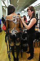 Mehron makeup artist applies body paint on model, at the Makeup Show NYC, in the Metropolitan Pavilion, May 15 2011.