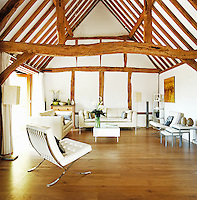 The original beams have been preserved and the living room furnished with a pair of matching sofas and Barcelona chairs