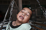 A boy with severe cataracts closes his eyes as he rocks back and forth on a swing at the Doc Son Pagoda orphanage in Hue, Vietnam. The orphanage is currently home to 170 children, some of whom have physical or mental disabilities. April 22, 2013.