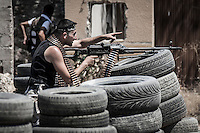 An opposition fighter targets with his machine gun to the enemy's position as Free Army rebels repel an offensive attack by Assad's army during a battle in the neighborhood of Jaser Al Nerab. Intensive combats have taken place in the area under control of the rebels close to the airport to regain the position lost by the Assad's troops.