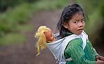 Three-year old Nely Roxana Miranda carries her blond doll on her back in Buena Vista Bacchuc, a small Mam-speaking Maya village in Comitancillo, Guatemala.