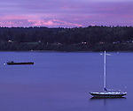 A purplish sunset tones the water and sky as a sailboat and barge are seen in the salt water.
