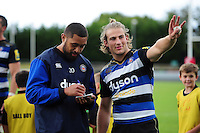 Taulupe Faletau of Bath Rugby signs an autograph with team-mate Max Clark. Pre-season friendly match, between the Scarlets and Bath Rugby on August 20, 2016 at Eirias Park in Colwyn Bay, Wales. Photo by: Patrick Khachfe / Onside Images