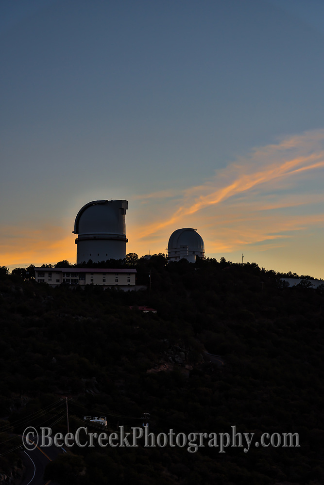 McDonald Observatory at sunset as the clouds light up with these colorful pinks and oranges over the tops of the two observatory in the skies over the Davis Mountains.