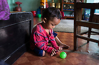Sujal Tamang (2) sits on the floor as he plays with a ball using his hands in his aunt's rented apartment in Jorpati, Kathmandu, Nepal on 2 July 2015. Sujal was buried under the rubble of his collapsed house for 36 hours before rescuers found him injured with a broken leg next to his mother who was killed on the spot. Photo by Suzanne Lee for SOS Children's Villages