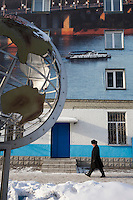Barnaul, Altai Region, Siberia, Russia, 24/02/2011..Globe of the Earth with Barnaul on top and city centre apartment building with wall covered by giant photo mural of the local River Ob.