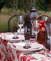 Individual lanterns on each place setting on a table laid for an alfresco autumnal supper