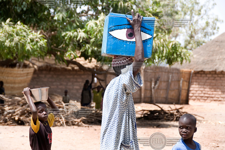 Jebel Touray carries equipment to be used for a trachoma operation at a patient's home.