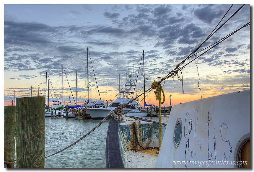 A weathered and worn shrimp boat points out to the waters at the harbor near Rockport and Fulton. This Texas Coast image was captured in the minutes before sunrise on a cool October morning.