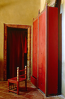In a rustic bedroom a contemporary wardrobe painted in deep vermilion contrasts with the mellow terracotta of the tiled floor