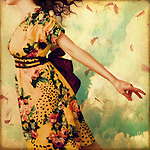 A young woman wearing a flowery summer dress who appears to be floating against a textured background