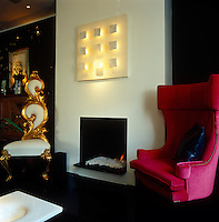 An ornately curlicued gilded chair is situated to one side of the minimalist fireplace contrasting with a contemporary wing-backed armchair on the other