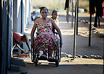 Delina Nleya gets a push from her son Nkosiyazi, 10, near their house in Bulawayo, Zimbabwe. Nleya suffered a spinal cord injury and uses a wheelchair provided by the Jairos Jiri Association with support from CBM-US.