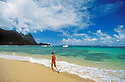 Woman walking on Tunnels beach with SCUBA diving tour boats behind; Haena, Kauai, Hawaii.