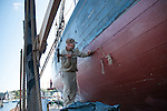 The Highlander Sea is being repaired at the Gloucester Marine Railway. She's a 154 foot wooden-hulled schooner, built in Essex, MA in 1924. John Hinckley hammers in new caulking with traditional tools.