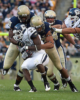 Pittsburgh defensive lineman Greg Romeus (91) and Jabaal Sheard (97) wrap up the UConn running back Jordan Todman (23). Pittsburgh Panthers defeat the University of Connecticut Huskies 24-21 on October 10, 2009 at Heinz Field, Pittsburgh, PA.