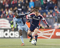 New England Revolution substitute midfielder Chad Barrett (9) hustles to disrupt clearing effort by Sporting Kansas City midfielder Lawrence Olum (13). In the first game of two-game aggregate total goals Major League Soccer (MLS) Eastern Conference Semifinal series, New England Revolution (dark blue) vs Sporting Kansas City (light blue), 2-1, at Gillette Stadium on November 2, 2013.