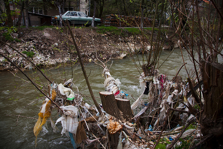Scenes of Travnik. Garbage collecting in the trees along the banks of a stream.