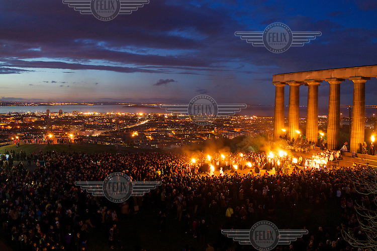 People gather in front of the National Monument on Carlton Hill in Edinburgh to celebrate the annaul Beltane Fire Festival. <br /> The Beltane Festival is an annual event when winter is purged by fire. From sunset on 30 April until early morning, over 300 volunteers create a dramatic reimagining of pagan gaelic folklore surrounded by a crowd of 6000 people. The May Queen arises to herald summer through a battle between elemental forces of order and chaos reaching a climax in the death of the green man in his winter form before bringing him back to life.