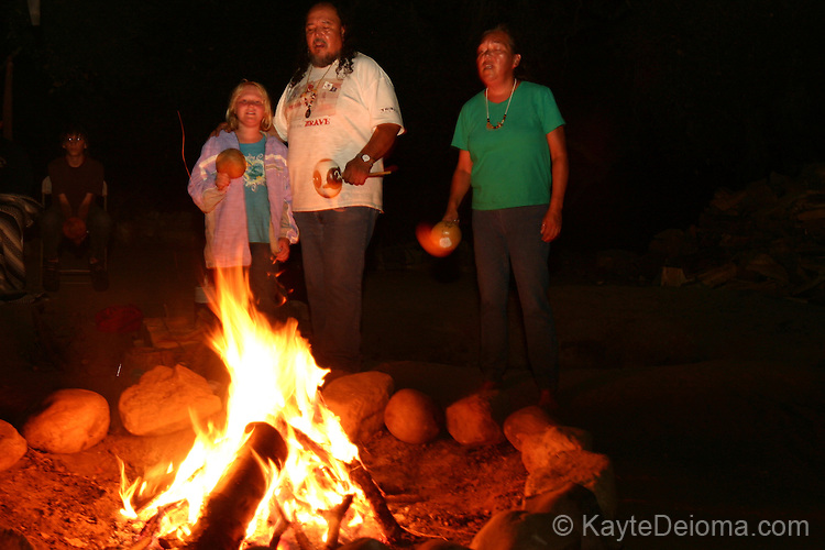 A Chumash elder and his sister and granddaughter sing around a fire circle in Thousand Oaks, CA