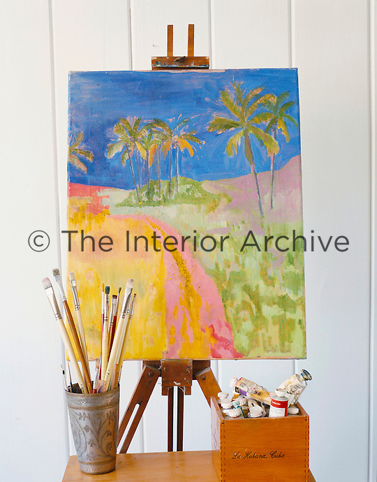 A brightly-coloured painting of a tropical landscape rests on an easel in the living room