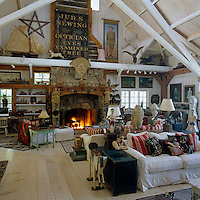 The vast barn-like living area is furnished with comfortable sofas and filled with Malcolm and Kelley McDowell's eclectic collection of American folk art