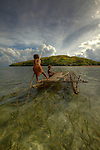 Children playing with a outrigger canoe in the village of Hessessai Bay at PanaTinai (Panatinane)island in the Louisiade Archipelago in Milne Bay Province, Papua New Guinea.  The island has an area of 78 km2..The Louisiade Archipelago is a string of ten larger volcanic islands frequently fringed by coral reefs, and 90 smaller coral islands located 200 km southeast of New Guinea, stretching over more than 160 km and spread over an ocean area of 26,000 km? between the Solomon Sea to the north and the Coral Sea to the south. The aggregate land area of the islands is about 1,790 km? (690 square miles), with Vanatinai (formerly Sudest or Tagula as named by European claimants on Western maps) being the largest..Sideia Island and Basilaki Island lie closest to New Guinea, while Misima, Vanatinai, and Rossel islands lie further east..The archipelago is divided into the Local Level Government (LLG) areas Louisiade Rural (western part, with Misima), and Yaleyamba (western part, with Rossell and Tagula islands. The LLG areas are part of Samarai-Murua District district of Milne Bay. The seat of the Louisiade Rural LLG is Bwagaoia on Misima Island, the population center of the archipelago.PanaTinai (Panatinane) is an island in the Louisiade Archipelago in Milne Bay Province, Papua New Guinea. The island has an area of 78 km2..The Louisiade Archipelago is a string of ten larger volcanic islands frequently fringed by coral reefs, and 90 smaller coral islands located 200 km southeast of New Guinea, stretching over more than 160 km and spread over an ocean area of 26,000 km? between the Solomon Sea to the north and the Coral Sea to the south. The aggregate land area of the islands is about 1,790 km? (690 square miles), with Vanatinai (formerly Sudest or Tagula as named by European claimants on Western maps) being the largest..Sideia Island and Basilaki Island lie closest to New Guinea, while Misima, Vanatinai, and Rossel islands lie further east..The archipelago is divided into the
