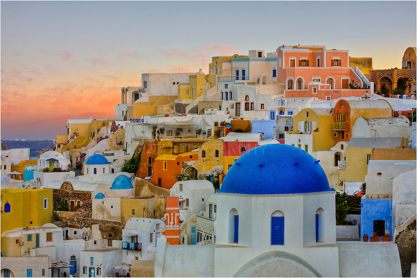 Evening in Oia, Santorini is magical. in this little village on island of Santorini, the sun sets into the Aegean allowing the pastel colors of the houses to really catch the eye.