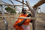 Angelina Methiang, a 42-year old refugee from the Nuba Mountains, works on a house she is building in Abyei, a town at the center of the contested Abyei region along the border between Sudan and South Sudan. Methiang's home in the Nuba Mountains was destroyed in 2012 by troops from the Republic of Sudan, and she fled for the relative safety of Abyei, where in 2011 soldiers and militias from the northern Republic of Sudan had swept through the area, chasing out tens of thousands of residents and looting and burning what was left behind. Although Ethiopian peacekeepers patrol the region, renewed attacks in Abyei by northern-backed Misseriya militias in 2013 have Methiang and others worried. The African Union has proposed a new peace plan for Abyei, including a referendum to be held in October 2013, but it has been rejected by the Misseriya and Khartoum. The Catholic parish of Abyei, with support from Caritas South Sudan and other international church partners, has maintained its pastoral presence among the displaced and assisted them with food, shelter, and other relief supplies.