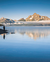 Lady in landscape, Grand Teton National Park.  Low lingering clouds and Mt Moran cast their reflection in Jackson Lake.