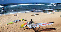 A windsurfer carries her windsurfing board towards the ocean at Ho'okipa Beach, Maui. (NOTE: the woman in the foreground is model released, the others are not model released.)