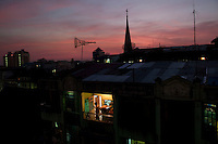 A man looks out of his balcony at dusk in Yangon.