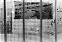 State of Palestine. West Bank. Balata Camp. Palestinian refugees. An elderly moslem woman wearing a Hijab looks outside of her window. Nobody is in the streets because the Israel Defense Forces (IDF, also called Tzahal or the military forces of the State of Israel) have impose a military curfew, which means that people are obliged to stay 24 hours into houses. The curfew can last for days and can only be lifted by the IDF when they decide to do it. A Hijab, also spelled ḥijāb, is a veil that covers the head and chest, which is often worn by Muslim women beyond the age of puberty in the presence of adult males outside of their immediate family as a form of modest attire. Balata Camp is a Palestinian refugee camp established in the northern West Bank in 1950, adjacent to the city of Nablus. It is the largest refugee camp in the West Bank. Balata Camp is densely populated with 30,000 residents in an area of 0.25 square kilometers. In 1991, Balata Camp was living under Isreal's occupation and rules as part as the Occuppied Territories. In the 1980s and 1990s, Balata residents played a leading role in the uprisings known as the First Intifada and the Second Intifada. Balata Camp is since 1993 under palestinian authority, located in the A zone. The Palestinian National Authority (PA or PNA) was the interim self-government body established to govern Areas A and B of the West Bank as a consequence of the 1993 Oslo Accords. Following elections in 2006, its authority had extended only in areas A and B of the West Bank. Since January 2013, the Fatah-controlled Palestinian Authority uses the name State of Palestine on official documents. © 1991 Didier Ruef
