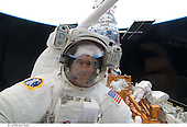 In Earth Orbit - May 15, 2009 -- Astronaut Michael Good, STS-125 mission specialist, peers through a window toward Atlantis' crew cabin interior, where his shirt-sleeved support team members busy themselves to aid the flight's second of five sessions of extravehicular activity to perform work on the Hubble Space Telescope. Astronaut Mike Massimino can be seen in the background at work on the port side of the shuttle's cargo bay..Credit: NASA via CNP