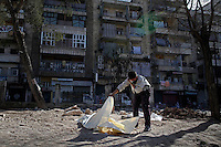 "A young boy attempts to make a positive identification on  one of the latest homicide victims to wash up on the shores of the Qweiq river - he will be buried in a shallow grave next to this recreation area...Cobbler's Park, a children's park in the Bustan Al-Qasr neighborhood of Aleppo under Free Syria Army control, has been renamed ""Martyr's Park"", since the revolution arrived in Aleppo in July of 2012.  A patch of dirt that lies next to children's swings, slides and monkey bars now serves as this neighborhood's makeshift cemetery. On January 29, 2011, 110 bodies floated down a water canal (which is part of the river Qweiq) that separates this rebel-controlled area from the regime side on the opposite side of the canal. Many of the showed signs of torture and most where executed with their hands bound behind their backs. In the weeks after this incident, dozens more bodies have been discovered in the canal - many of the victims that have not been claimed by family members have been buried here."