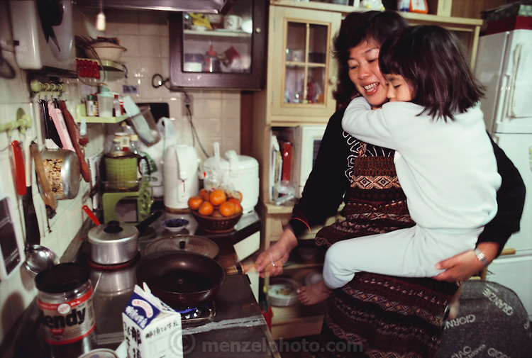 Sayo Ukita cooks breakfast while holding six-year-old Maya. Japan. Published in Material World: A Global Family Portrait, page 50. The Ukita family lives in a 1421 square foot wooden frame house in a suburb northwest of Tokyo called Kodaira City.
