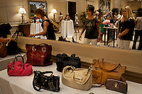 """Newport, California, July 22, 2011 - Women peruse the designer handbags at The Divorcee Sale at the Pelican Hill Resort in Orange County. Organized by Jill Alexander, the sale offers luxury items most of which from uber-rich divorcees looking to unload their proverbial baggage. The event also donates 25 percent of its profits to breast cancer research...Alexander, who has actually never been married, started The Divorcee Sale this past spring after noticing a trend amongst her friends and colleagues going through divorces. """"Many women have an attachment to these things and they just want to move on,"""" says Alexander. She added that the consignment shops were full and not really offering much in the way of sympathy in the situation. Alexander is different in that she visits the home of the divorcees, often with cakes and tissues, and acts as both a consignor and a confidant. ."""