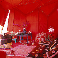 Inside the rooftop tent an armchair is trimmed with cowrie shells and the cushions are covered in tribal textiles and serve as a sleeping area