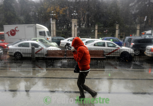 People protect themselves from the cold during a heavy temporal in Madrid on January 7, 2010. (c)PEDRO ARMESTRE