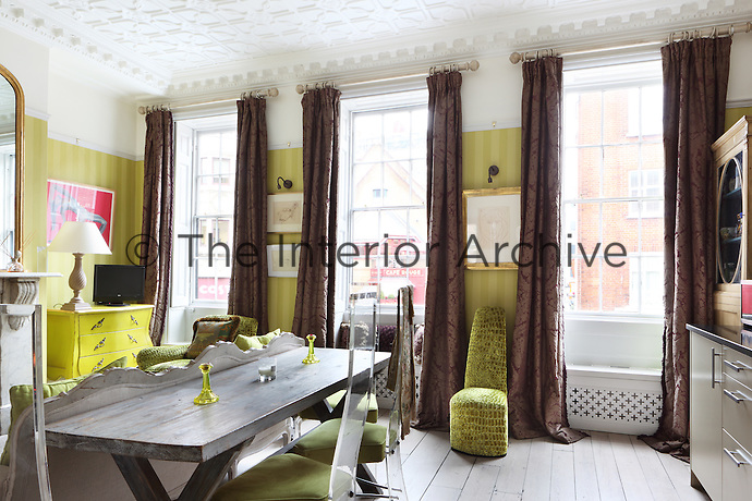 The living/dining room of a flat within a converted Georgian house, which still retains its ornate platerwork ceiling and floor to ceiling windows. The room is furnished with modern furniture and furnishings in bronze and green tones.