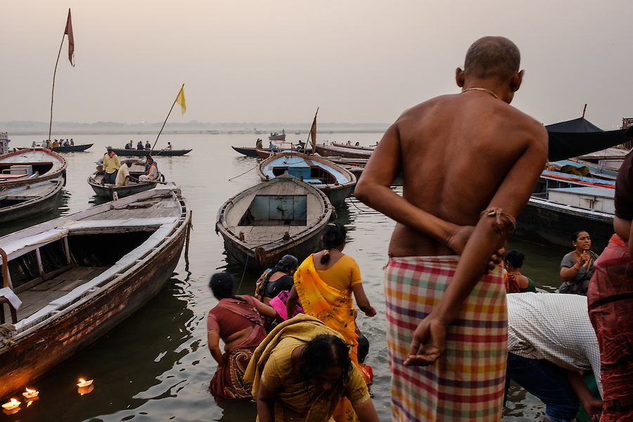 VARANASI, INDIA - CIRCA NOVEMBER 2016: People worshiping and bathing in the Ganges river. Varanasi is the spiritual capital of India, the holiest of the seven sacred cities and with that many rituals and offerings are performed daily by priests and hindus.