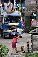 A woman chops wood as a truck drives past  in a village on a corner of the Interoceanic Highway in the Amazon.