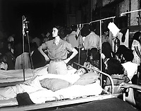 1st Lt. Phyllis Hocking adjusts glucose injection apparatus for a GI patient in the 36th Evac. Hospital, Palo, Leyte, P.I., quartered in the Church of the Transfiguration, as the congregation kneels during Christmas Eve services.  December 24, 1944.  (Army Staff)<br /> NARA FILE #:  319-CE-124-237580<br /> WAR &amp; CONFLICT BOOK #:  922