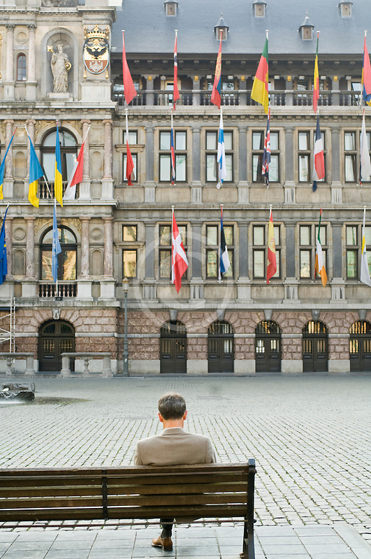 Belgium, Antwerp, Man sitting alone on bench in Grote Markt in front of Town Hall, Stadhuis