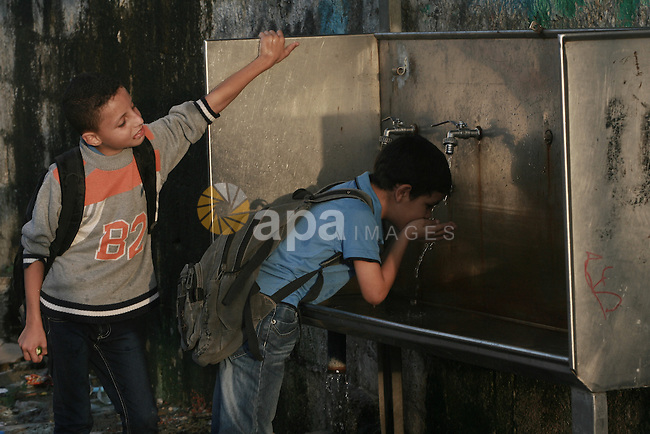 Palestinian boys drink water from a public tap in Rafah refugee camp in southern Gaza Strip, Oct. 30, 2013. The United Nations Relief and Works Agency for Palestine Refugees (UNRWA) has removed food aid for 9,558 families in Gaza since the beginning of the year, while adding only 5,430 new families to the programme. Photo by Eyad Al Baba