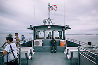 Residents and visitors return to Kwajalein Island from Ebeye on the free ferry operated by the U.S. Army. Only a few people have permission to enter the military base. Most of the foreigners that work on Ebeye travel to Kwajalein to catch a flight from the international airport that is located there and used by both military and civil aviation.
