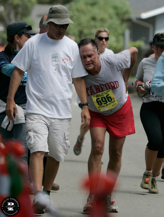 Philip Smith (696) of Sausalito leans on a medical official as he attempts to cross the finish line at the 99th running of the Dipsea Race at Sintson Beach State Park in Stinson Beach, Calif. on Sunday June 14th, 2009...